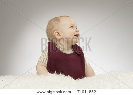 Adorable little baby smiling, sitting on the white blanket, studio shot, isolated on grey background, lovely baby in bib