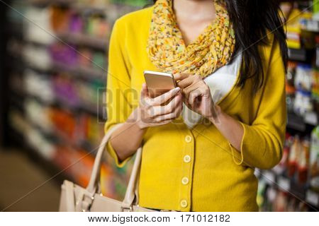 Mid section of woman using mobile phone in grocery section of supermarket