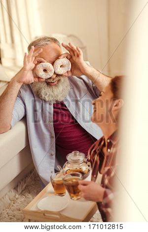 Mature man and woman sitting on carpet drinking tea and fooling around