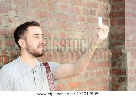Young latin man taking a selfie in a park. Outdoors.
