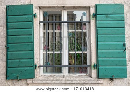 white wooden window green shutters with railing in Kotor, Montenegro