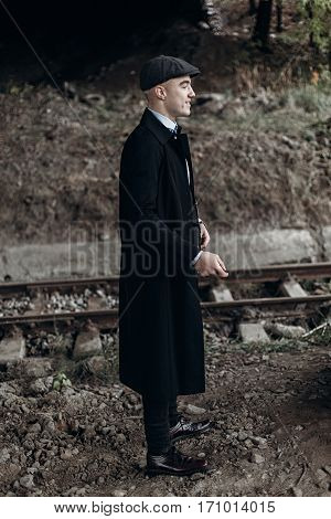 Stylish Man In Retro Look Smiling Posing On Background Of Railway. England In 1920S Theme. Fashionab