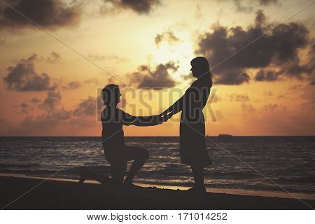 romantic marriage proposal at sunset tropical beach