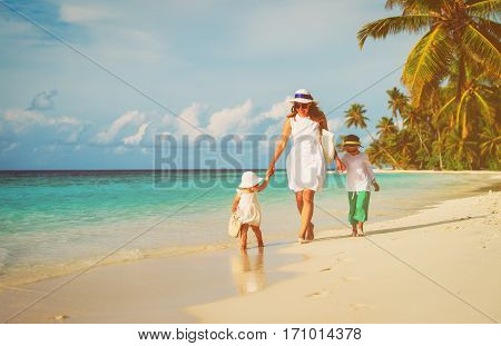 mother with little son and daughter walk on beach, family beach vacation