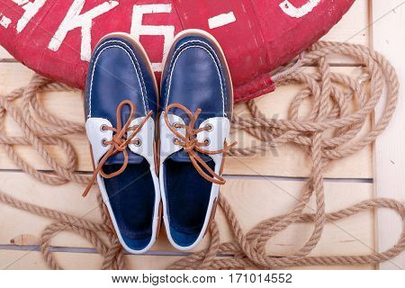 Blue boat shoes on wooden background near lifebuoy and rope. Top view.