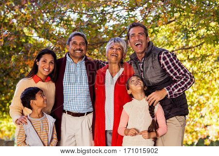 Cheerful multi-generation family laughing while standing at park during autumn