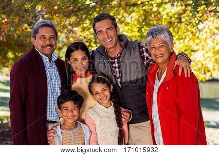 Portrait of smiling multi-generation family standing at park during autumn