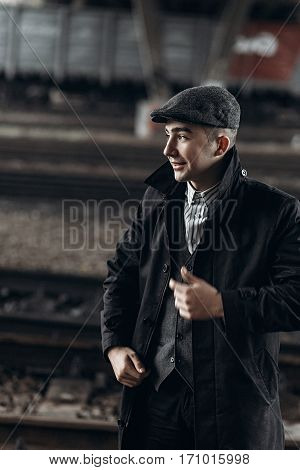 Stylish Man In Retro Outfit Smiling, Posing On Background Of Railway. England In 1920S Theme. Fashio