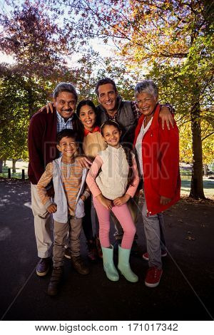 Full length of smiling multi-generation family standing at park during autumn