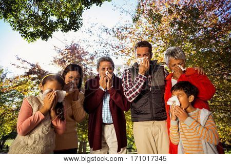Low angle view of sick family blowing their noses at park