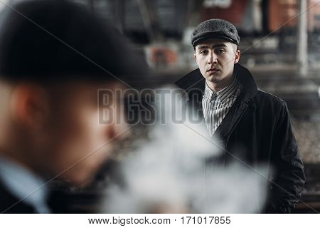 Brutal Gangsters Posing On Background Of Railway. England In 1920S Theme. Fashionable Confident Man