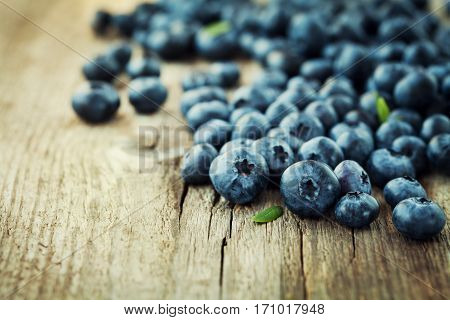 Blueberry, great bilberry or bog whortleberry on wooden rustic board.
