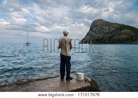 Fisherman with two rods on the shore on the background of mountain sea and cloudy sky in the evening. The elderly person fishes. Novy Svet Crimea.