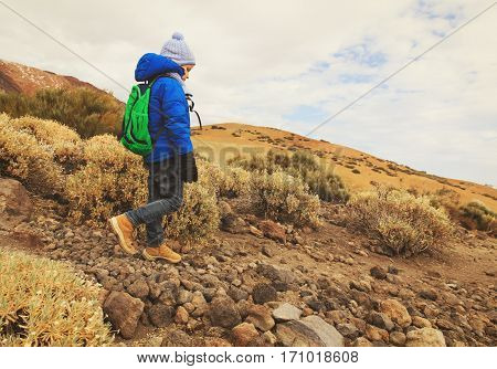little boy with backpack hiking in mountains, family travel