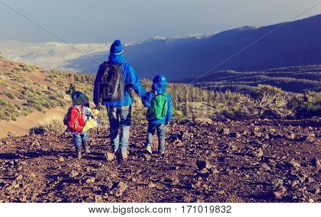 father with two kids travel in mountains, family travel