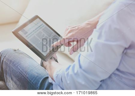 surf the Internet. Pleasant man sititng on the couch and using tablet while reading news