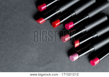 Set of matte Lipstick in red and natural colors on black background. Fashion colorful lipsticks. Professional makeup and beauty. Frame. Top view. Copy space.