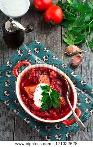 Beetroot soup with meat sour cream and parsley in a brown ceramic bowl on the old wooden background. Borsch- traditional dish of Ukrainian cuisine. Selective focus.Top view.