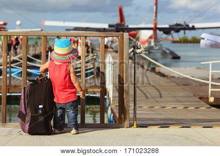 little girl waiting for seaplane, family travel concept