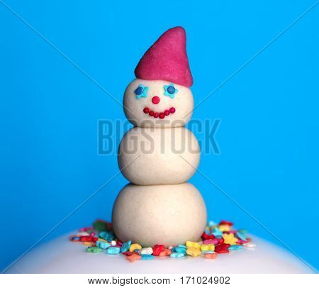 marzipan snowman in red hat closeup on blue background