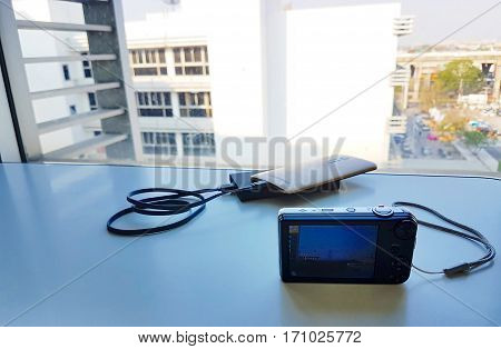 Compact digital camera on a white table with a city landscape background,Focus on holding camera capture a city landscape,Copy space,Vintage style,Low light style,photographer camera,photographer