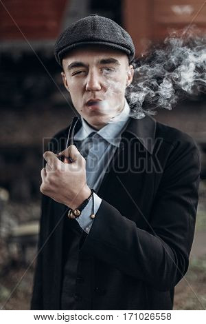 Sherlock Holmes Look, Man In Retro Outfit, Smoking Wooden Pipe. England In 1920S Theme. Fashionable