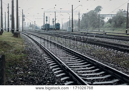 Railway Tracks. Transportation Roads And Platform With Carriage. Foggy Rainy Atmosphere On Railroad.