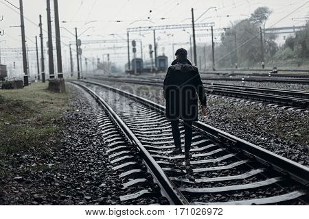 Silhouette Of Stylish Man In Retro Look Walking In Rain On Background Of Foggy Railway. England In 1