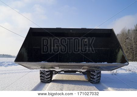 big bucket front loader in winter frosty day against the blue sky