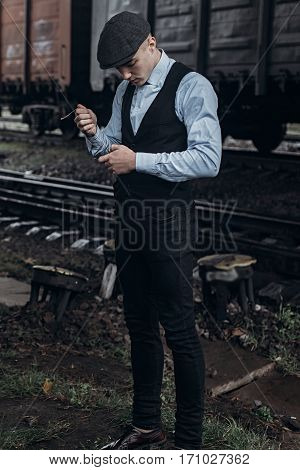 stylish man in retro look smiling posing on background of railway. england in 1920s theme. fashionable brutal confident gangster. atmospheric moments