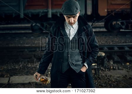 stylish gangster man with bottle whiskey in retro look posing on background of railway carriage. england in 1920s theme. fashionable brutal confident man