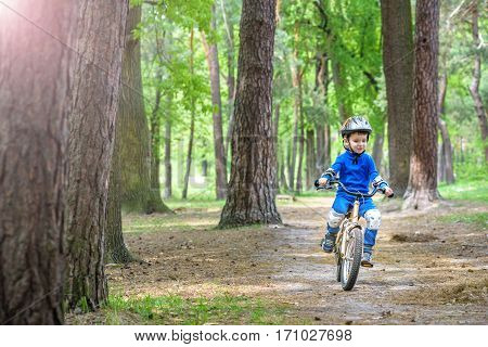 Happy Cute Blond Kid Boy Having Fun His First Bike On Sunny Summer Day, Outdoors.  Child Making Spor