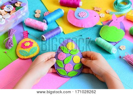 Child made Easter egg decor from felt. Small child holds a felt Easter egg decor in his hands. Easter crafts set, handicraft tools and materials on a table. Holiday spring crafts concept