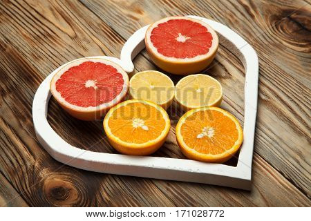 Citrus fruit in a heart on a wooden background