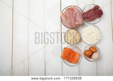 Proteins fish cheese eggs meat and chicken on a white wooden background