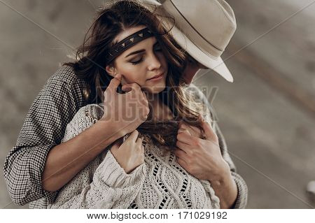 Handsome Cowboy Man In White Hat Touching Cheek Of Beautiful Boho Gypsy Woman With Leather Headband,