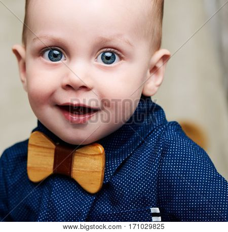 Cute caucasian baby boy wearing a fashionable blue shirt and a wooden bowtie all while looking straight into the camera with a positive smile on his face, along with his large blue eyes.