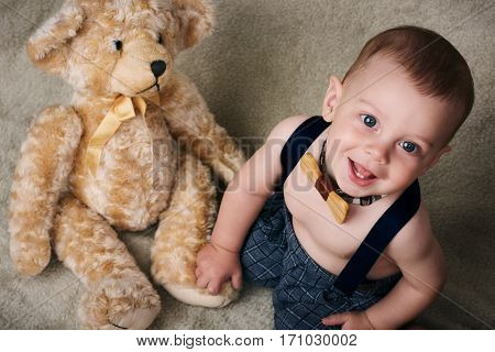 Beautiful caucasian baby boy sitting on the floor wearing a wooden bowtie while holding his soft teddy bear with a large smile on his face.