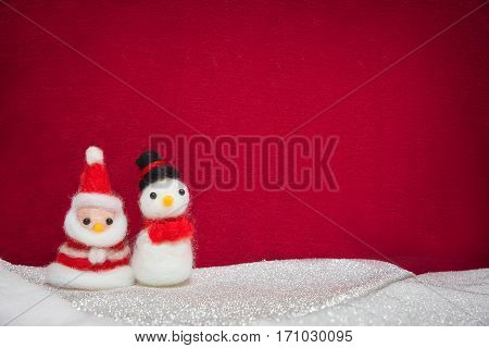 Santa claus snowman wool doll on snow set up with red cloth backdrop happy new year and christmas concept background with copy space