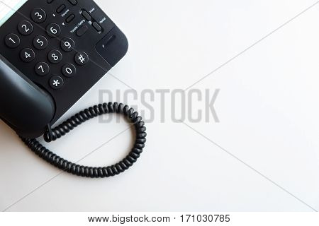 Top view or flat lay of digital voip black telephone on white table call center contact center customer service customer support concept background with copy space selective focus on dialing pad