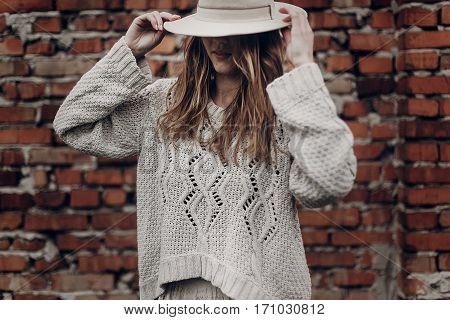 Stylish Brunette Woman In White Hat And Boho White Sweater Posing Near Red Brick Wall