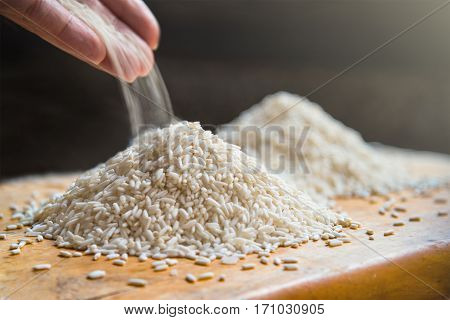 Hand pouring rice on pile of white rice on wooden table background metaphor ingredient nutrition carbohydrate food concept selective focus