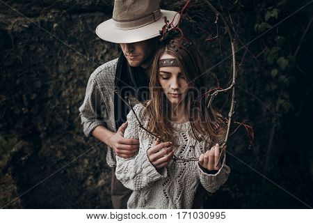 Stylish Hipster Couple Tender Hugging. Boho Gypsy Woman Holding Branch And Man In Hat Embracing Her.