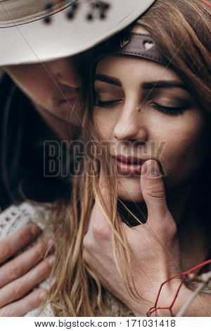 Stylish Hipster Couple Portrait. Boho Gypsy Woman And Man In Hat Embracing Her Lips Closeup. Atmosph