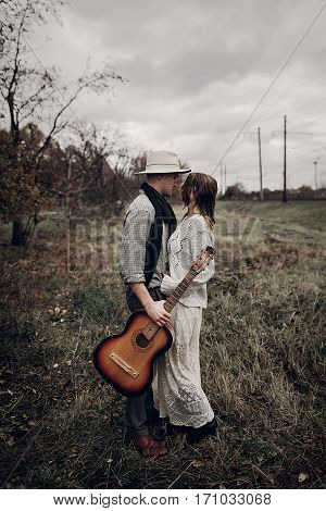 Stylish Hipster Couple Hug In Field, Handsome Cowboy Musician With Guitar And Indie Style Woman In W