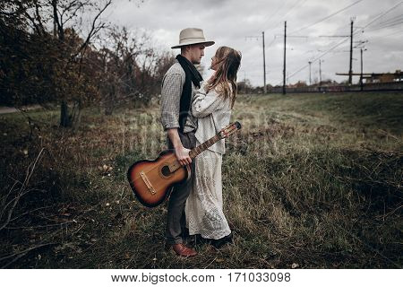 Rustic Wedding Concept. Boho Gypsy Woman And Man With Guitar Posing In Windy Field. Stylish Hipster