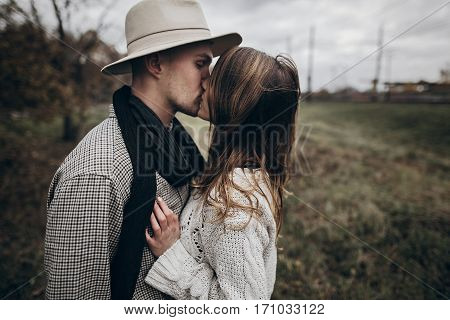Rustic Wedding Concept. Boho Gypsy Woman And Man In Hat Kissing In Windy Field. Stylish Hipster Coup