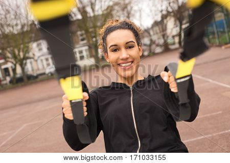 young woman exercising outdoors with a suspension trainer