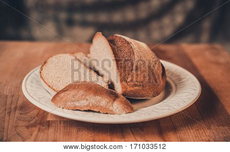 Rye bread on a wooden table. Top view. Fresh fragrant crispy sliced bread. Loaf of bread slices on cutting board closeup. Home-made bread on an white porcelain plate.