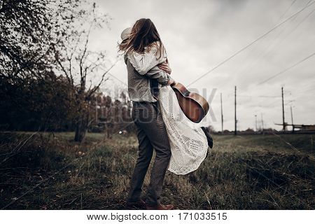 Stylish Hipster Couple Dancing In Windy Field. Boho Gypsy Woman And Man In Hat Embracing In Windy Fi